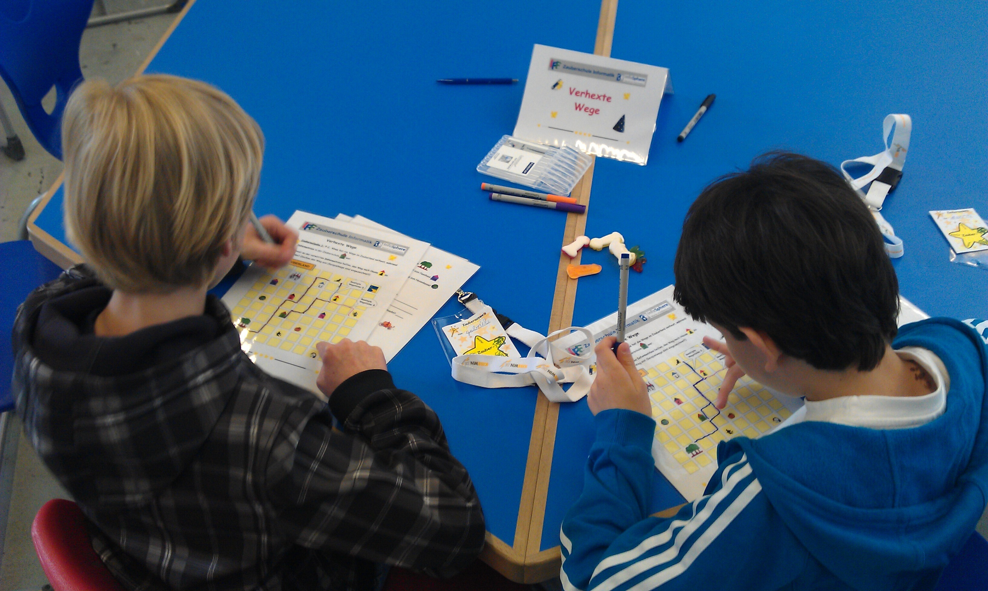 "Children solving the game ""Verhexte Wege"""