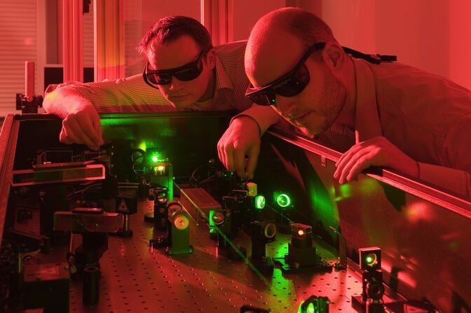Researchers and a laser